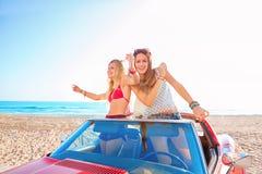 Schöne Parteifreundmädchen, die in ein Auto auf dem Strand tanzen Stockfotos