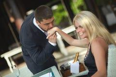 Schöne, reizende, junge Paare im Restaurant Küssen der Hand von w Stockbild