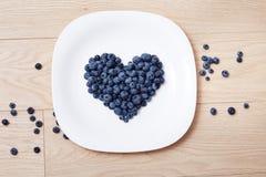 Schöne saftige reife natürliche organische Himbeerbrombeerblaubeeren und tadellose blaue Tischdecke punktiert weißes Tellerherz-F Lizenzfreies Stockfoto