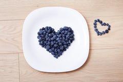 Schöne saftige reife natürliche organische Himbeerbrombeerblaubeeren und tadellose blaue Tischdecke punktiert weißes Tellerherz-F Stockbilder