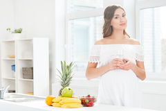 Schöne schwangere Frau in der Küche, die ein Glas Wasser hat Lizenzfreie Stockbilder