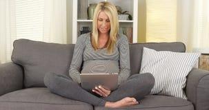 Schöne schwangere Frau, die auf Couch unter Verwendung der Tablette sitzt Lizenzfreie Stockfotografie