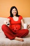 Schöne schwangere Frau, die auf der Couch sitzt Lizenzfreie Stockfotografie