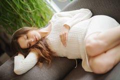 Schöne schwangere Frau, die an der Couch sitzt Stockfotografie