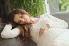 Schöne schwangere Frau, die an der Couch sitzt Lizenzfreie Stockfotografie