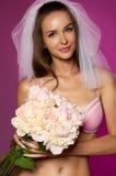 Schöne sexy Braut mit dem langen dunklen Haar in einem weißen Schleier, rosa Spitzewäsche mit Blumenstrauß von blassem - rosa Pfi Stockbild