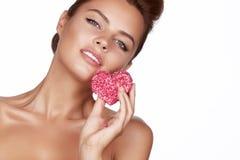 Schöne sexy Brunettefrauenessenkuchenform des Herzens auf einem weißen Hintergrund, gesundes Lebensmittel, geschmackvoller, organ Lizenzfreie Stockbilder