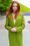 Schöne sexy Frau mit dem brennenden roten Haar mit grünem Mantel gehend durch die Straßen der Stadt Lizenzfreie Stockfotos