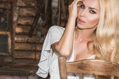 Schöne sexy Frau mit dem langen gelockten blonden Haar, den grünen Augen recht süß und den sexy vollen Lippen auf dem wilden West Stockfoto