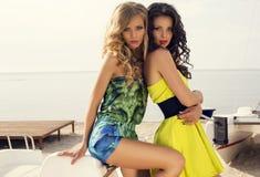 Schöne sexy Mädchen in den Kleidern, die auf Strand aufwerfen Stockfotografie