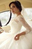 Schöne sinnliche Braut mit dem dunklen Haar im luxuriösen Spitzehochzeitskleid Stockfotos