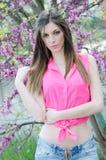 Schöne Sitzdame zwischen Blütenbaum in der purpurroten Farbe Lizenzfreie Stockfotografie
