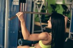 Schöne Sitzfrau, die in der Turnhalle - Mädchen in der Eignung ausarbeitet Stockfotografie