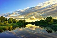 Schöne Sonnenuntergang-Landschaft mit Reflexion auf Fluss-Himmel und Wolken Stockfotos