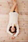 Schöne sorglose junge zufällige Frau, die auf dem Boden liegt. Stockfoto