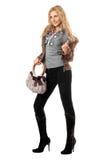 Schöne spielerische junge Blondine mit einer Handtasche Stockbilder