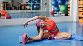 Schöne Sportfrau, die Eignungübung an der Sportgymnastik ausdehnend tut yoga Lizenzfreies Stockfoto