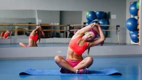 Schöne Sportfrau, die Eignungübung an der Sportgymnastik ausdehnend tut yoga Stockfoto