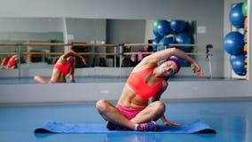 Schöne Sportfrau, die Eignungübung an der Sportgymnastik ausdehnend tut yoga Stockbilder