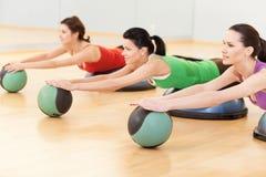 Schöne sportliche Frauen, die Übung auf Ball tun Lizenzfreies Stockbild