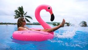Schöne trinkende Kokosnuss der jungen Frau und Entspannung auf einer rosa aufblasbaren Matratze in einem Swimmingpool - hübsches  stock video
