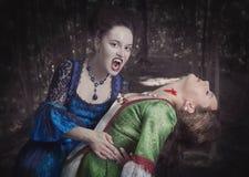 Schöne Vampirsfrau im mittelalterlichen Kleid und in ihrem Opfer Stockbilder