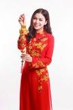 Schöne vietnamesische Frau mit roter AO Dai, das glückliche Verzierung des neuen Jahres - Stapel Gold hält Lizenzfreie Stockbilder