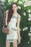 Schöne vorbildliche Aufstellung des jungen Mädchens nahe blühenden Fliedern am Frühling Lizenzfreies Stockfoto