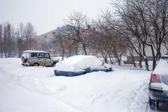 Schnee auf Autos nach Schneefällen Städtische Szene des Winters Stockfotografie