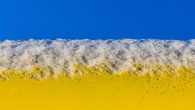 Schnee auf einem gelben Rohr Lizenzfreie Stockbilder