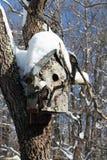 Schnee auf einem handgemachten Vogelhaus Stockbild