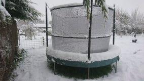 Schnee auf einer Trampoline im hinteren Garten lizenzfreies stockfoto