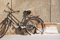 Schnee bedeckte altes blakc Fahrrad, das gegen eine strukturierte Wand, Changchun, China geparkt wurde Lizenzfreies Stockfoto
