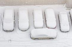 Schnee bedeckte Auto im Parkplatz Städtische Szene Nach einem Schneesturm Säubern Sie Automobil vom Schnee Stockfotografie