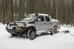 Schnee bedeckte Auto im Wald im Winter Lizenzfreie Stockfotos