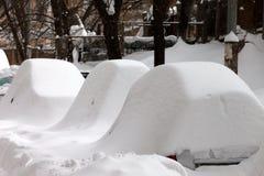 Schnee bedeckte Autos nach Schneefällen Stockbilder