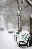 Schnee bedeckte Bänke im Winterpark Stockfoto