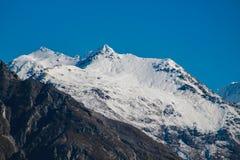 Schnee bedeckte Bergspitze mit klarem blauem Himmel mit einer Kappe stockfotografie