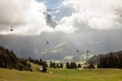Schnee bedeckte Bergspitzen und Drahtseilbahnen in Grindelwald, die Schweiz Stockfotografie