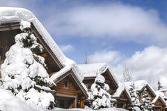 Schnee bedeckte Dachspitzen von Berghütten im Pfeifer stockfotos