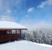 Schnee bedeckte das Blockhaus, das über dem Winter-Horizont schaut Lizenzfreie Stockfotos