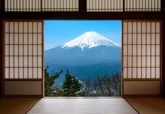 Schnee bedeckte den Fujisan in Japan mit einer Kappe, das durch den traditionellen Japaner gesehen wurde, der Papiertüren schiebt lizenzfreie stockbilder