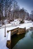 Schnee bedeckte Eisenbahnbrücke über einem Nebenfluss in ländlicher Carroll Count Stockfotos