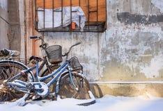 Schnee bedeckte Fahrräder gegen eine strukturierte Wand in einem Schnee bedeckten Changchun, China Lizenzfreie Stockfotos