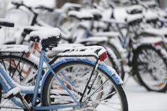 Schnee bedeckte Fahrräder im Parkplatz Stockfoto