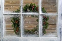 Schnee bedeckte Fenster mit dekorativem Weihnachtskranz auf Fenster Lizenzfreies Stockfoto