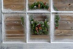 Schnee bedeckte Fenster mit dekorativem Weihnachtskranz auf rustikalem w Stockbilder
