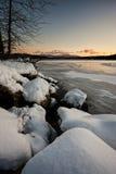 Schnee bedeckte Flusssteine durch den See Lizenzfreies Stockfoto