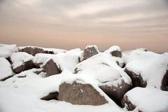 Schnee bedeckte Flusssteine unter einem bewölkten Sonnenuntergang stockfotos