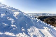 Schnee bedeckte gebrochenes von den Windhügeln in den Bergen in kaltem sonnigem Lizenzfreie Stockbilder